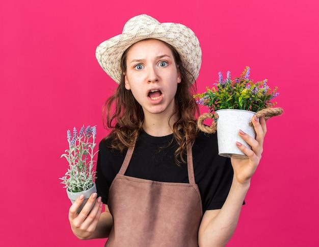Jovem jardineira assustada usando chapéu de jardinagem e segurando flores em vasos