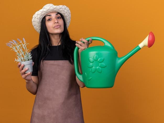 Jovem jardineira caucasiana confiante usando uniforme e chapéu segurando um vaso de flores e um regador isolado na parede laranja