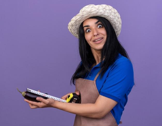 Jovem jardineira caucasiana impressionada usando uniforme e chapéu em pé na vista de perfil medindo berinjela com medidor de fita adesiva
