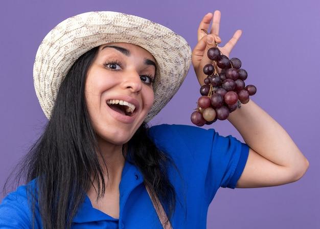 Jovem jardineira caucasiana impressionada usando uniforme e chapéu segurando cacho de uva