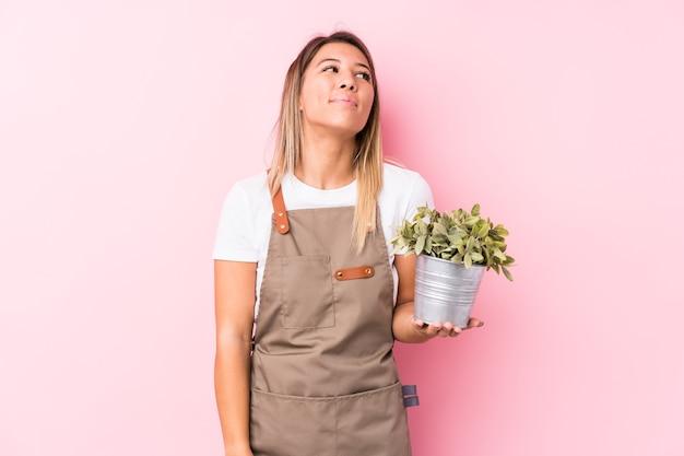 Jovem jardineira caucasiana isolada sonhando em alcançar objetivos e propósitos