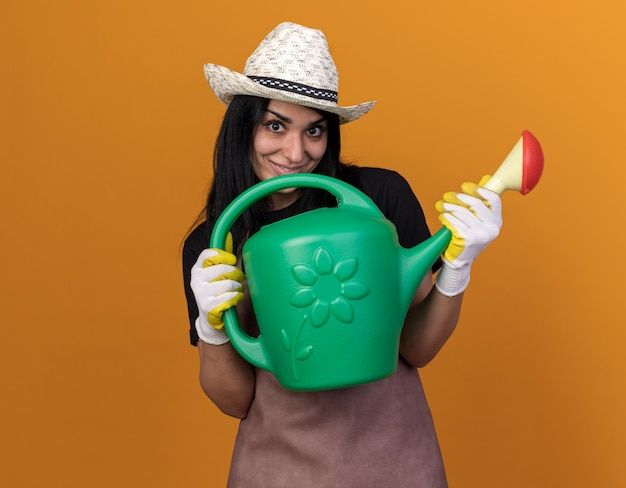 Jovem jardineira caucasiana satisfeita usando uniforme e chapéu com luvas de jardineiro segurando um regador