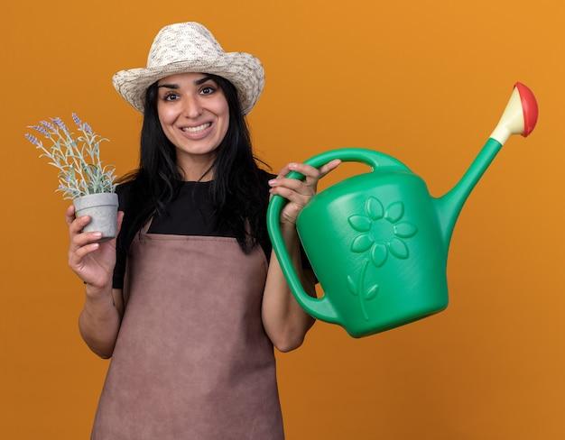 Jovem jardineira caucasiana sorridente, usando uniforme e chapéu, segurando um vaso de flores e um regador
