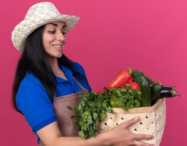 Jovem jardineira caucasiana sorridente, vestindo uniforme e chapéu, em vista de perfil, segurando e olhando para uma cesta de legumes