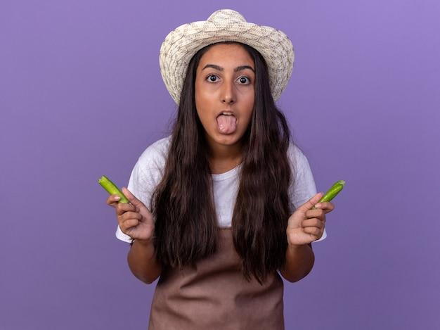 Jovem jardineira com avental e chapéu de verão segurando pimenta verde preocupada e animada, mostrando a língua em pé sobre a parede roxa