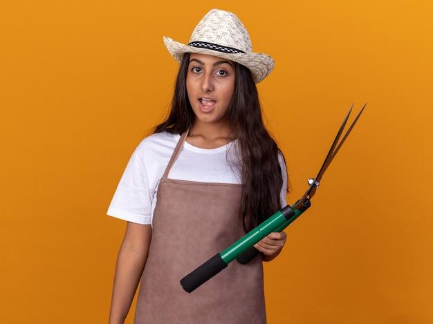 Jovem jardineira com avental e chapéu de verão segurando um cortador de cerca viva espantada e surpresa em pé sobre a parede laranja