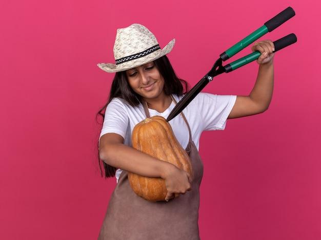 Jovem jardineira com avental e chapéu de verão segurando uma abóbora e um cortador de cerca viva sorrindo com uma cara feliz em pé sobre a parede rosa
