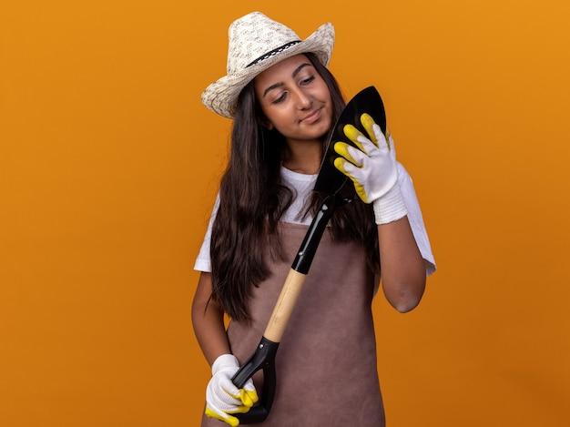 Jovem jardineira com avental e chapéu de verão segurando uma pá olhando para ela com um sorriso no rosto em pé sobre a parede laranja