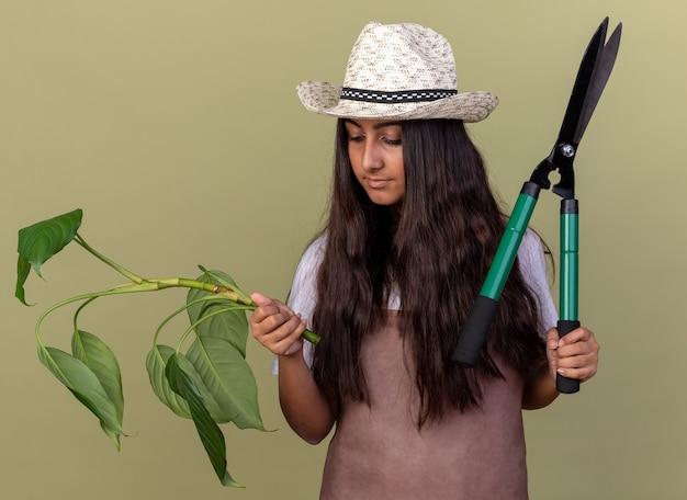 Jovem jardineira com avental e chapéu de verão segurando uma tesoura de planta e cerca-viva, parecendo confiante em pé sobre a parede verde