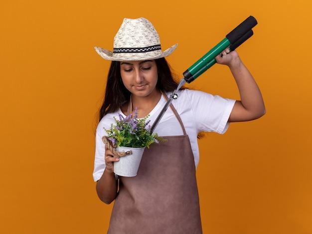 Jovem jardineira com avental e chapéu de verão segurando uma tesoura de sebes e um vaso de plantas, sorrindo confiante em pé sobre a parede laranja