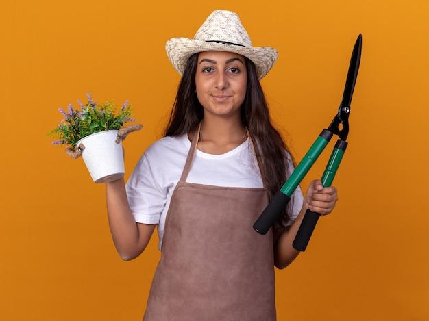 Jovem jardineira com avental e chapéu de verão segurando uma tesoura de sebes e uma planta em um vaso com um sorriso no rosto em pé sobre uma parede laranja