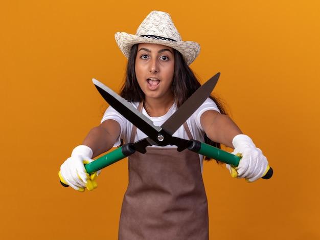 Jovem jardineira com avental e chapéu de verão segurando uma tesoura de sebes surpresa e espantada de pé sobre a parede laranja