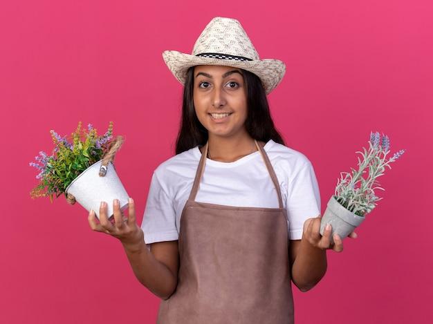 Jovem jardineira com avental e chapéu de verão segurando vasos de plantas e sorrindo com uma cara feliz em pé sobre a parede rosa