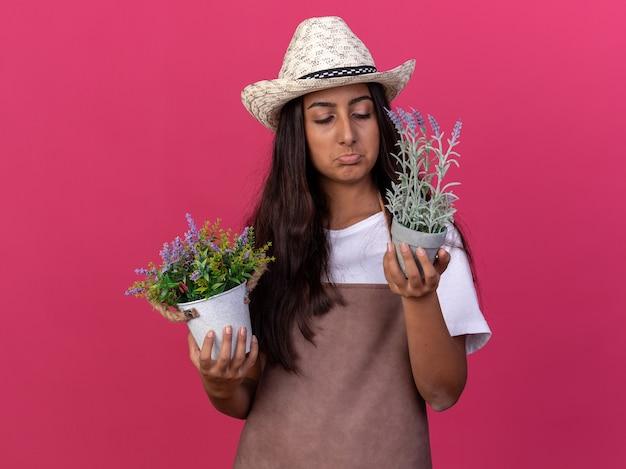 Jovem jardineira com avental e chapéu de verão segurando vasos de plantas olhando para ela e ficando descontente e triste em pé sobre a parede rosa