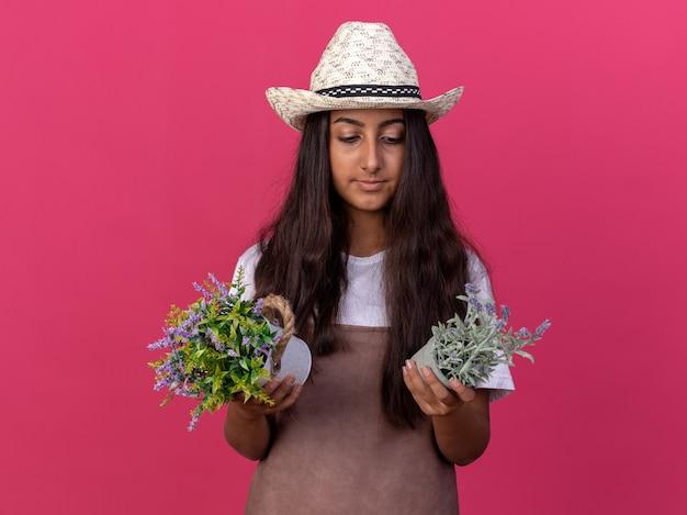 Jovem jardineira com avental e chapéu de verão segurando vasos de plantas olhando para eles com uma cara séria em pé sobre a parede rosa