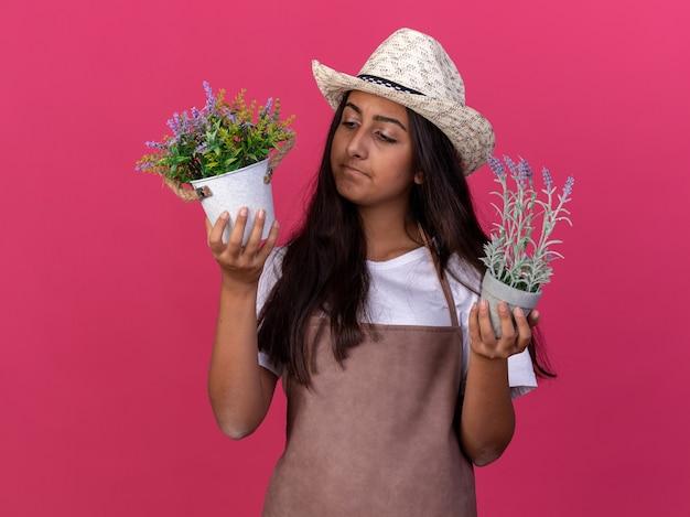 Jovem jardineira com avental e chapéu de verão segurando vasos de plantas olhando para eles confusos em pé sobre uma parede rosa