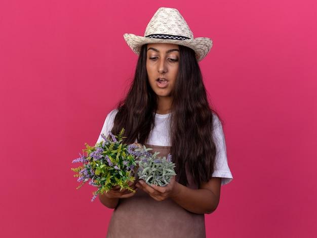 Jovem jardineira com avental e chapéu de verão segurando vasos de plantas olhando para eles surpresa em pé sobre a parede rosa