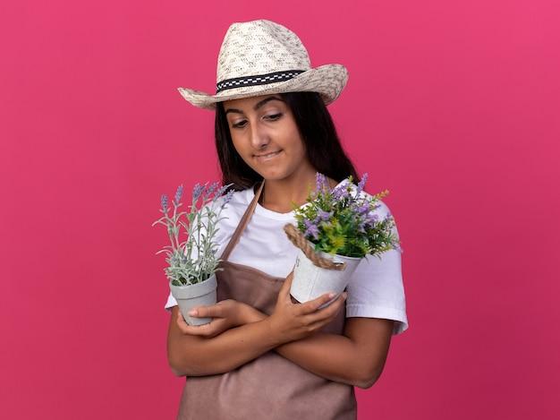 Jovem jardineira com avental e chapéu de verão segurando vasos de plantas, parecendo confiante, sorrindo com um sorriso no rosto em pé sobre a parede rosa