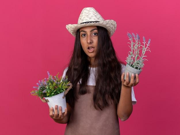 Jovem jardineira com avental e chapéu de verão segurando vasos de plantas surpresa e maravilhada em pé sobre uma parede rosa