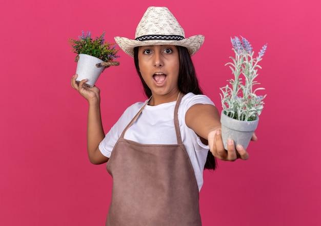 Jovem jardineira com avental e chapéu de verão segurando vasos de plantas surpresa em pé sobre a parede rosa
