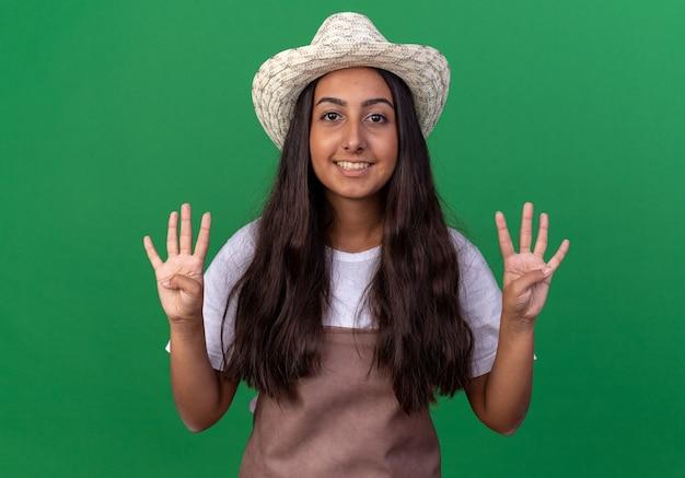 Jovem jardineira com avental e chapéu de verão sorrindo e mostrando o número oito em pé sobre a parede verde