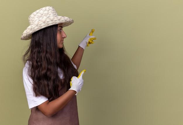 Jovem jardineira com avental e chapéu de verão, usando luvas de trabalho, apontando com o dedo indicador para o lado em pé sobre a parede verde