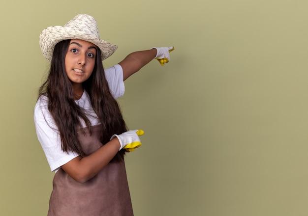 Jovem jardineira com avental e chapéu de verão usando luvas de trabalho apontando com o dedo indicador para o lado lookign confusa em pé sobre a parede verde