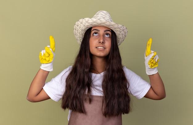 Jovem jardineira com avental e chapéu de verão usando luvas de trabalho apontando para cima com o dedo indicador olhando para cima com um sorriso no rosto em pé sobre a parede verde