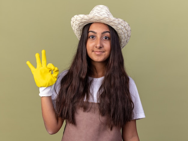 Jovem jardineira com avental e chapéu de verão usando luvas de trabalho e sorrindo com uma cara feliz, mostrando a placa de ok em pé sobre a parede verde