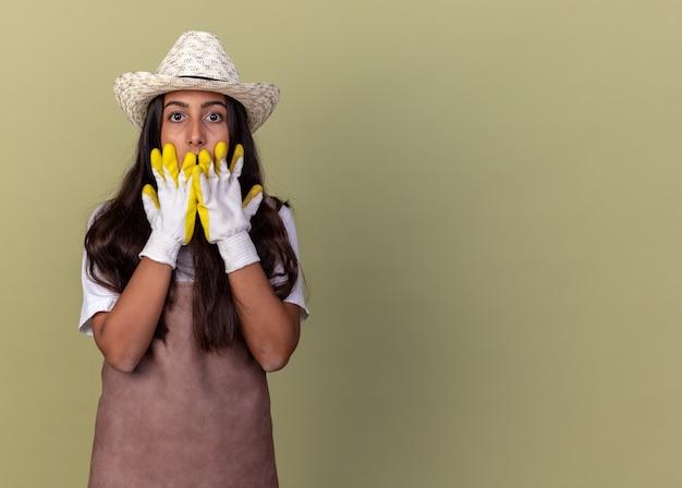 Jovem jardineira com avental e chapéu de verão, usando luvas de trabalho, levando um choque, cobrindo a boca com as mãos em pé sobre a parede verde