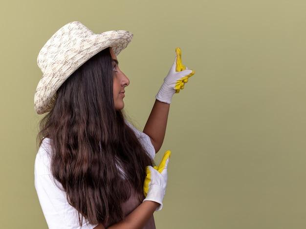 Jovem jardineira com avental e chapéu de verão usando luvas de trabalho, olhando para o lado com uma expressão cética apontando com o dedo indicador para algo em pé sobre a parede verde