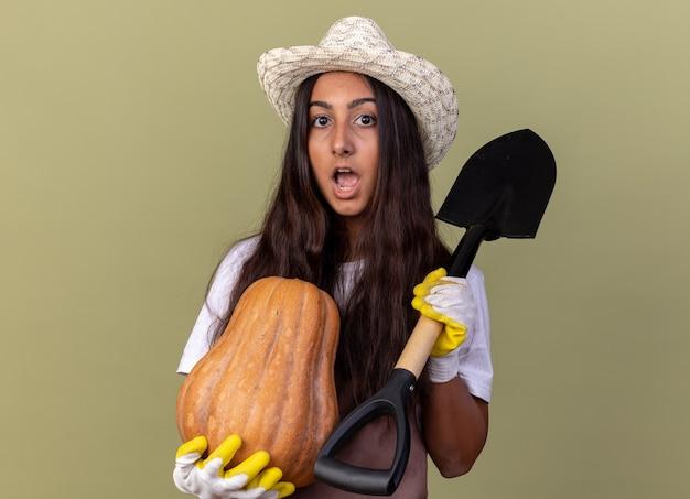 Jovem jardineira com avental e chapéu de verão usando luvas de trabalho segurando uma abóbora e uma pá espantada e surpresa em pé sobre a parede verde
