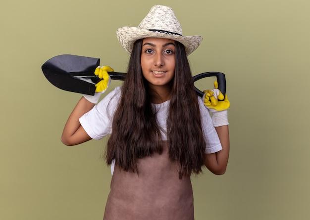 Jovem jardineira com avental e chapéu de verão usando luvas de trabalho segurando uma pá e sorrindo confiante em pé sobre a parede verde