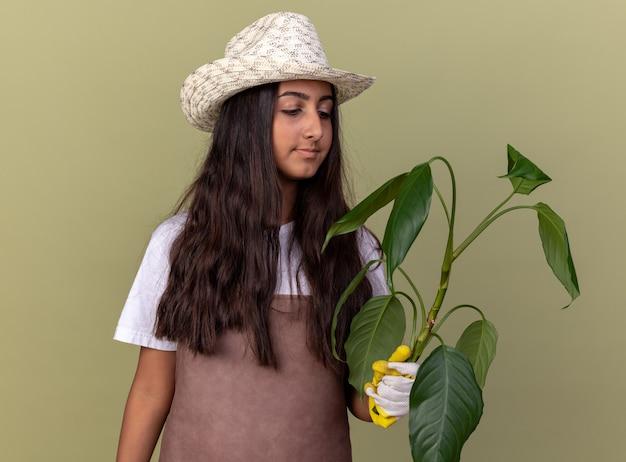 Jovem jardineira com avental e chapéu de verão usando luvas de trabalho segurando uma planta olhando para ela com um sorriso no rosto em pé sobre a parede verde