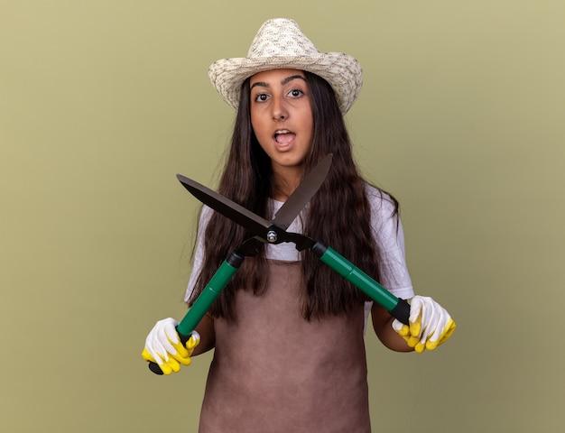 Jovem jardineira com avental e chapéu de verão, usando luvas de trabalho, segurando uma tesoura de cerca viva, feliz e surpresa em pé sobre a parede verde