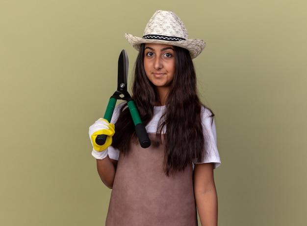 Jovem jardineira com avental e chapéu de verão usando luvas de trabalho segurando uma tesoura de cerca-viva sorrindo confiante em pé sobre a parede verde
