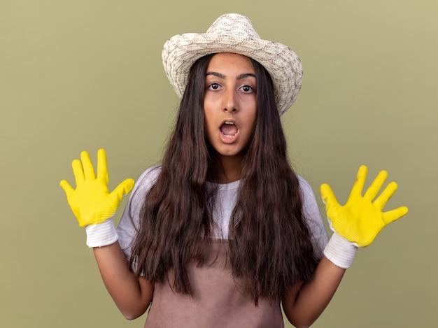 Jovem jardineira com avental e chapéu de verão usando luvas de trabalho, surpresa e preocupada, levantando as mãos em sinal de rendição em pé sobre a parede verde