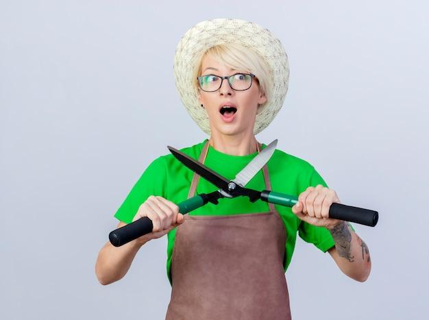 Jovem jardineira com cabelo curto, avental e chapéu segurando o aparador de cerca viva aparentando ser surpreendida
