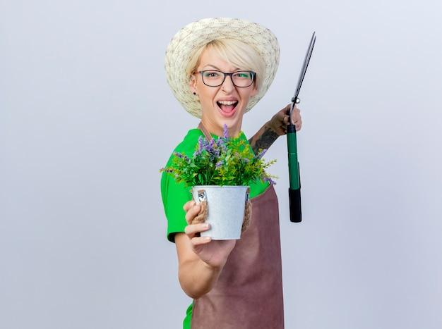Jovem jardineira com cabelo curto, avental e chapéu segurando um cortador de cerca viva mostrando um vaso de plantas sorrindo com uma cara feliz