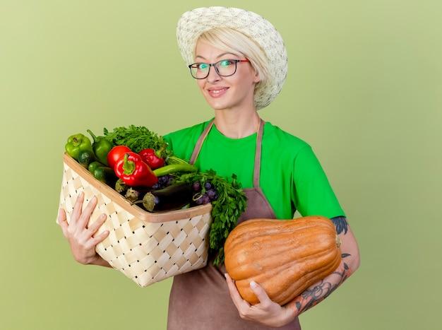 Jovem jardineira com cabelo curto, avental e chapéu segurando uma abóbora e uma caixa cheia de legumes, olhando para a câmera, sorrindo alegremente em pé sobre um fundo claro