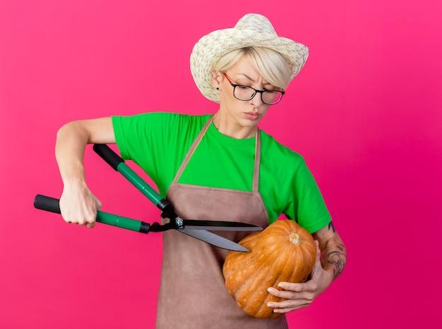 Jovem jardineira com cabelo curto, avental e chapéu segurando uma abóbora