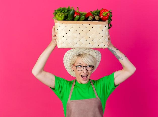 Jovem jardineira com cabelo curto, avental e chapéu segurando uma caixa cheia de legumes