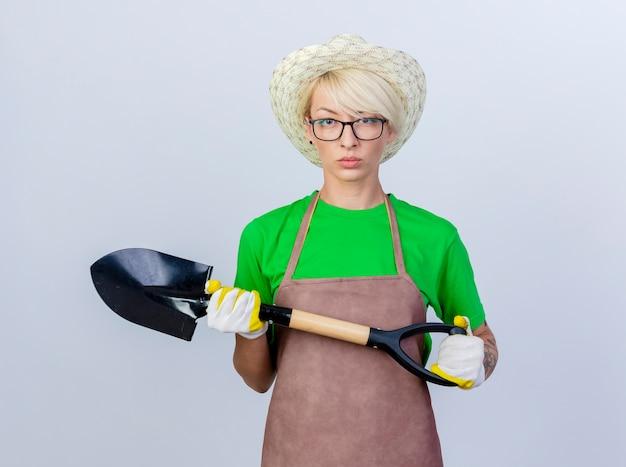 Jovem jardineira com cabelo curto, avental e chapéu segurando uma pá com uma cara séria