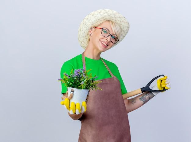 Jovem jardineira com cabelo curto, avental e chapéu segurando uma pá e um vaso de plantas com um sorriso no rosto