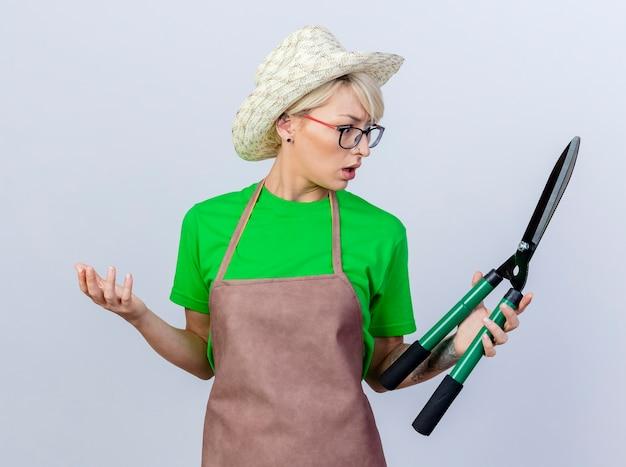 Jovem jardineira com cabelo curto, avental e chapéu segurando uma tesoura de cerca viva, olhando para eles sendo confusos em pé sobre um fundo branco