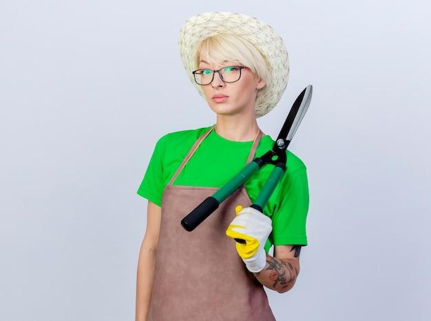 Jovem jardineira com cabelo curto, avental e chapéu segurando uma tesoura de sebes com cara séria