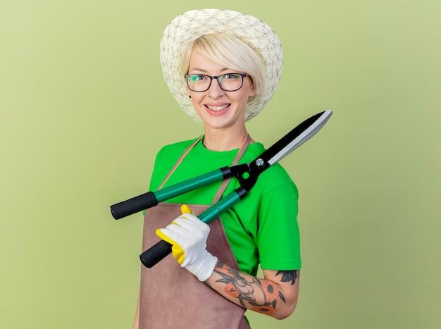 Jovem jardineira com cabelo curto, avental e chapéu segurando uma tesoura de sebes, olhando para a câmera, sorrindo alegremente em pé sobre um fundo claro
