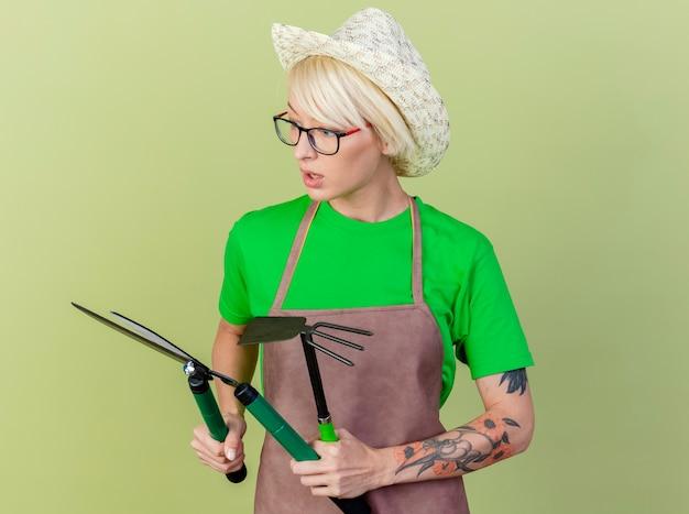 Jovem jardineira com cabelo curto, avental e chapéu segurando uma tesoura de sebes, olhando para ela intrigada de pé sobre um fundo claro