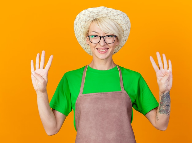 Jovem jardineira com cabelo curto no avental e chapéu aparecendo e apontando para cima com os dedos número oito sorrindo em pé sobre um fundo laranja