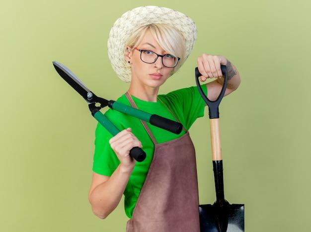 Jovem jardineira com cabelo curto no avental e chapéu segurando equipamentos de jardinagem, olhando para a câmera com uma cara séria em pé sobre um fundo claro